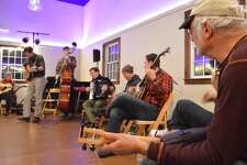 """Bart Goldberg of Westport, at right, play along on the ukulele at the Westport Country Playhouse's """"Woody Sez"""" hootenanny, Friday, Dec. 8, 2017, in Westport, Conn."""