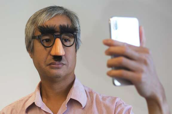 In this Monday Oct. 30, 2017, photo, Associated Press reporter Anick Jesdanun demonstrates Face ID, Apple's name for its facial-recognition technology, on an iPhone X, in New York. If you're wearing glasses, the iPhone can still recognize you using other parts of your face, within reason. The iPhone did not recognize Jesdanun with this costume on. (AP Photo/Mark Lennihan)