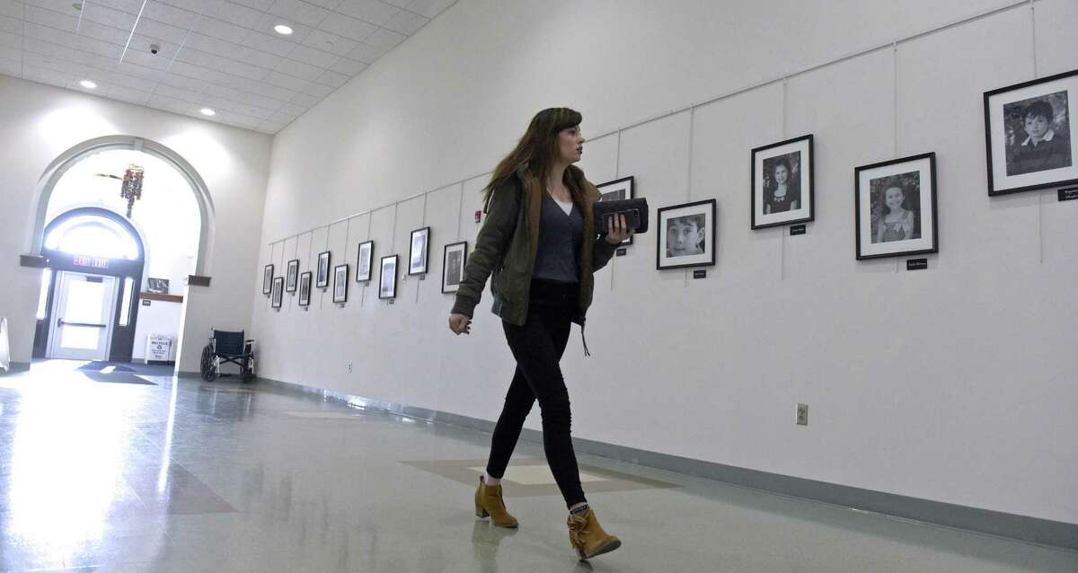 Chloe Helena, of Sandy Hook, walks through a gallery of photographs of the victims of Sandy Hook Elementary School shooting at the Newtown Municipal Center on Wednesday.