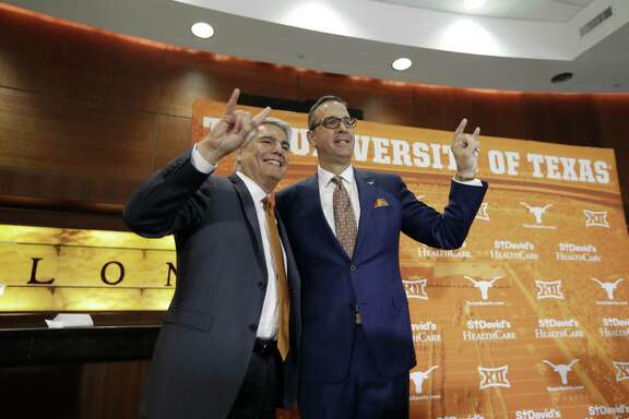 Texas president Greg Fenves, left, and Chris Del Conte, right, hold up the Hook'em sign as they pose for a photo following a news conference where DelConte was introduced at the new vice president and athletics director for the University of Texas, Monday, Dec. 11, 2017, in Austin, Texas. (AP Photo/Eric Gay)