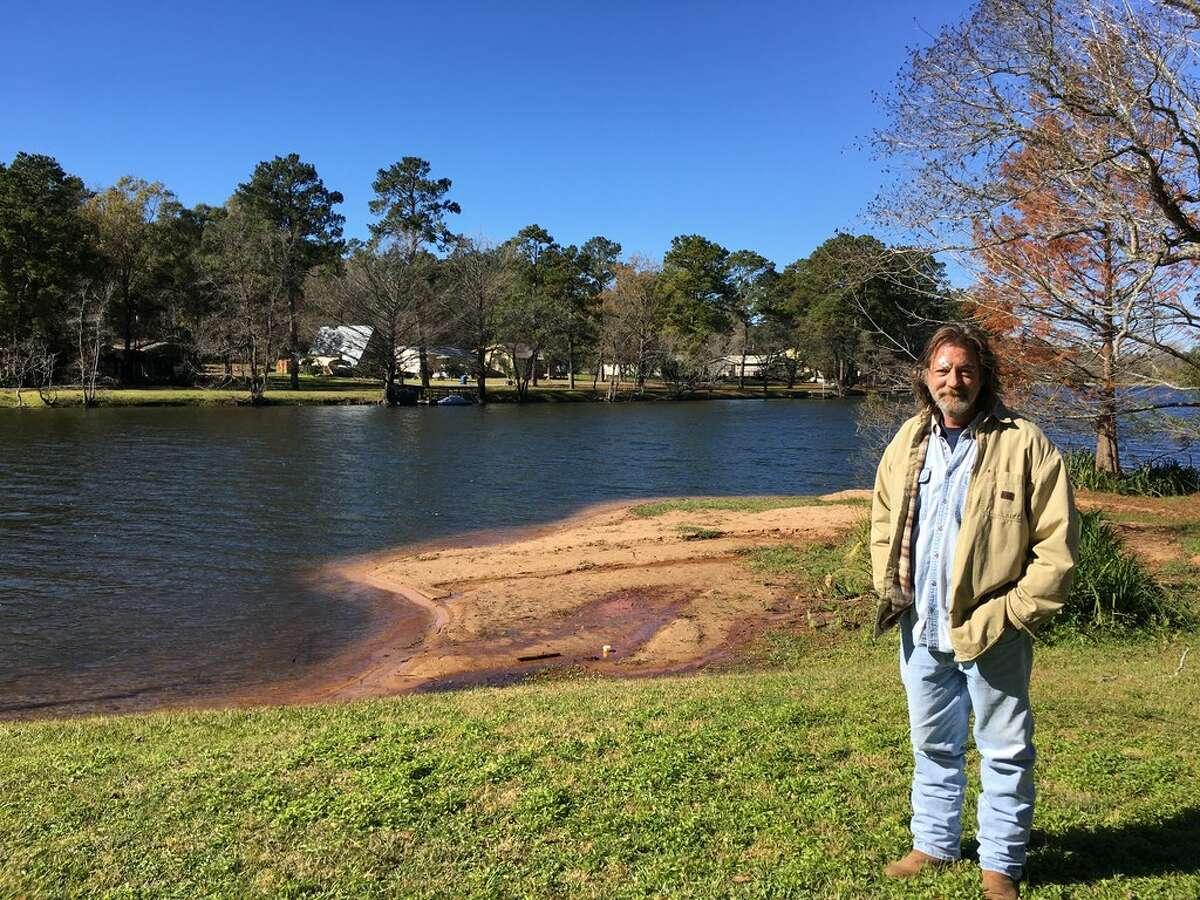Troy Schroeder stands at the edge of Pine Lake about 10 miles west of Conroe in December, 2017. Schroeder and his neighbors oppose the city's plan to annex their development.