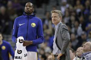 Golden State Warriors' Kevin Durant, left, and head coach Steve Kerr during the second half of an NBA basketball game against the Portland Trail Blazers Monday, Dec. 11, 2017, in Oakland, Calif. (AP Photo/Marcio Jose Sanchez)
