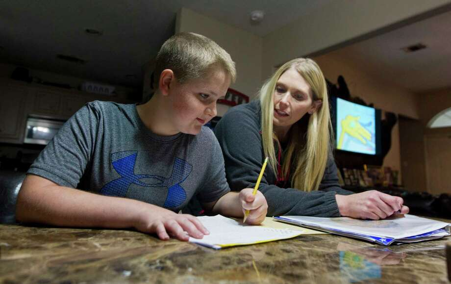 Kristy Heckendorn helps her son Braden, 11, with his homework Thursday, Dec. 7, 2017, in Montgomery. Braden Heckendorn, born right-hand dominant, is having to learn to use his left hand for writing and other functions after a pellet gun projectile to the chest in 2013 sent him into cardiac arrest, resulting in a traumatic brain injury and leaving him legally blind. Ten months after receiving three, intravenous infusions of his mesenchymal stem cells in January 2017, Heckendorn's vision and motor functions have improved. Photo: Jason Fochtman, Staff Photographer / © 2017 Houston Chronicle