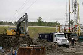 Workers with Haz Mat Special Services LLC remove soil Wednesday, Dec. 13, 2017, in Missouri City after an oil well blow out at the Panther #1 oil rig on FM 2234 near the Fort Bend Parkway Toll Road.