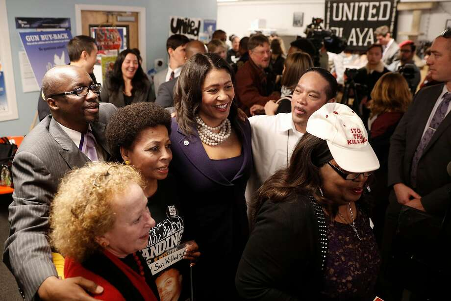 San Francisco acting Mayor London Breed (center) poses for photographs after meeting with members of the United Playaz, an organization promoting a gun buy-back program happening this weekend. Photo: Michael Macor, The Chronicle