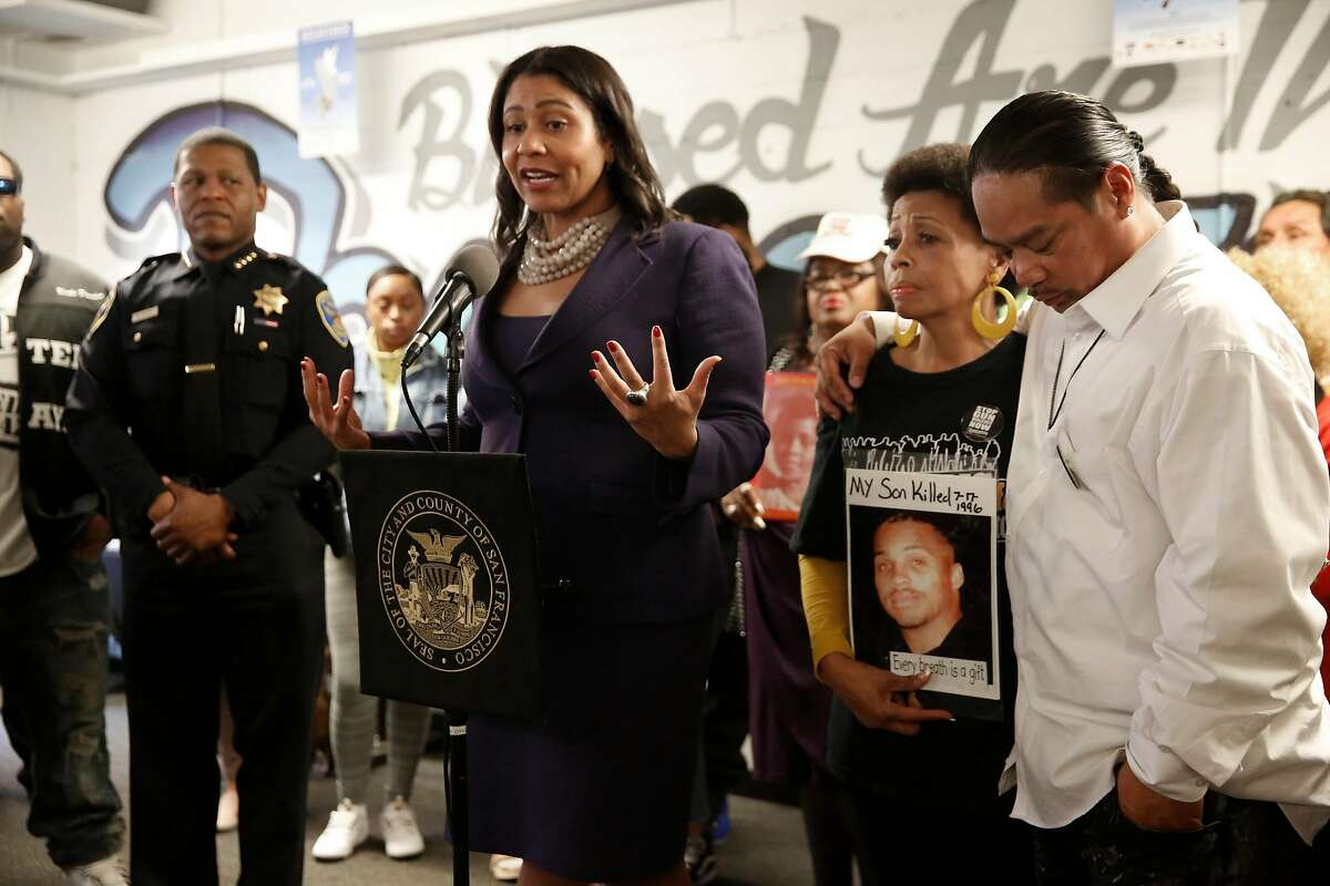 POlice CHiefr William Scott, (left) joins Acting Mayor of San Francisco London Breed during a meeting with members of the United Palayaz, on Wednesday December 13, 2017, to promote a gun buy back program happening this weekend in San Francisco, Calif. Mattie Scott holds a photograph of her son she lost to gun violence in 1996 as United Playaz director Rudy Corpuz comforts her.