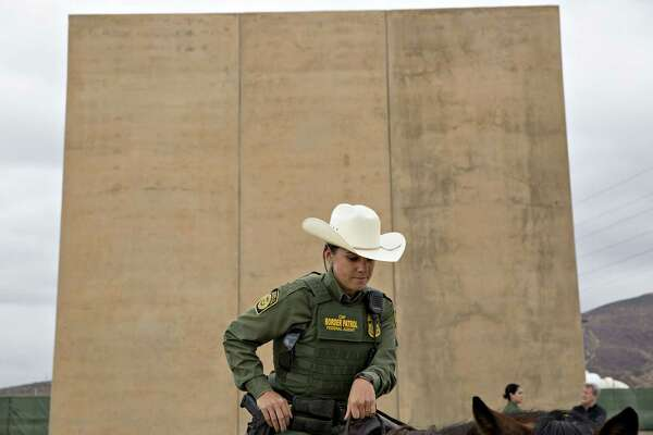 A U.S. Border Patrol agent sits on a horse in front of a U.S.-Mexico border wall prototype in San Diego on Oct. 30.