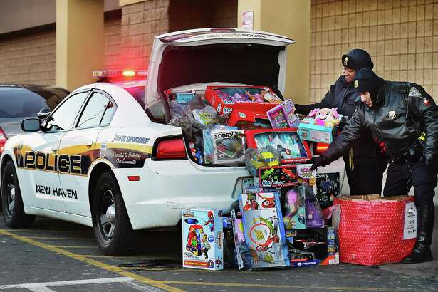 """New Haven police Capt. Patricia Helliger and Officer Eli Mendez load up a cruiser with donated toys from a collection box at the Walmart in New Haven Wednesday at the """"Stuff The Cruiser Toy Drive!"""" The New Haven Police Department will accept family-friendly toys, games, puzzles, coats, hats and monetary donations at the Walmart from 10 a.m. to 4 p.m. today. Toys also can be dropped off at the New Haven Police Substation at 26 Charles St. For information, contact Helliger at 203-668-8087 or Metashar Dillon at 860-785-4332."""