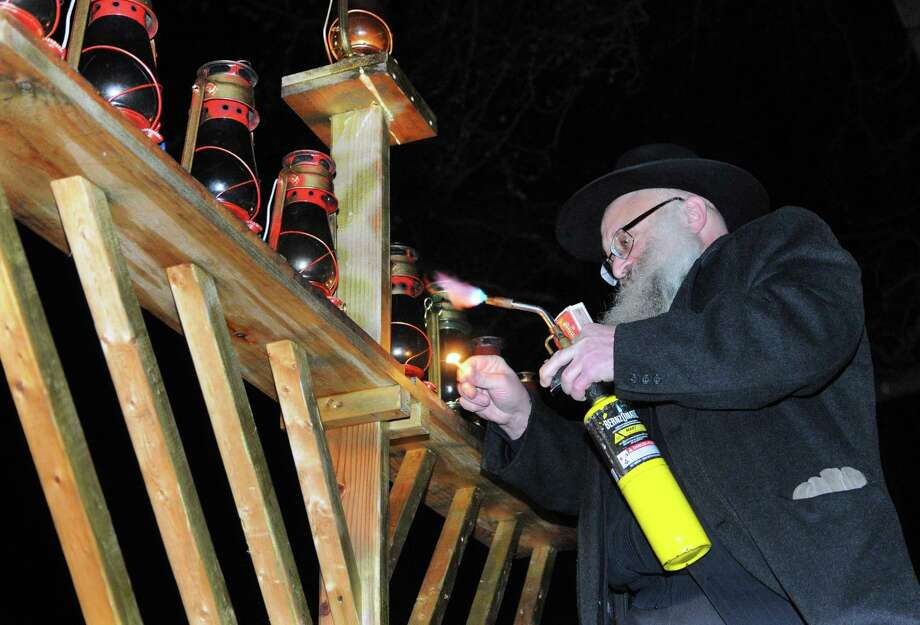 Rabbi Joseph Stock lights the Menorah during Mishkan Day Camp's 28th annual Lighting of the Menorah in front of the Trumbull Town Hall Steps to celebrate Hanukkah in Trumbull, Conn. on Wednesday Dec. 13, 2017. Mishkan Israel Day Camp was opened in Bridgeport in 1945 under the direction of rabbi Israel Stock and his wife. It branched out to include Stamford and other Fairfield County communities in 1975. Photo: Christian Abraham / Christian Abraham / Connecticut Post