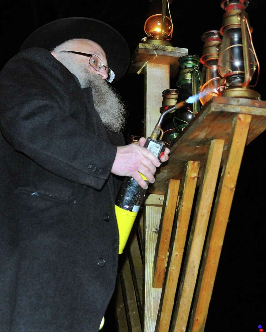 Rabbi Joseph Stock lights the Menorah during Mishkan Day Camp's 28th annual Lighting of the Menorah in front of the Trumbull Town Hall Steps to celebrate Hanukkah in Trumbull, Conn. on Wednesday Dec. 13, 2017. Mishkan Israel Day Camp was opened in Bridgeport in 1945 under the direction of rabbi Israel Stock and his wife. It branched out to include Stamford and other Fairfield County communities in 1975.