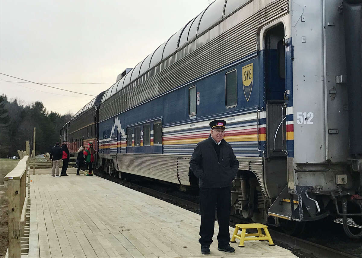 Train conductor stands beside The Train To Christmas Town at Stony Creek Ranch Resort, Dec. 2017, in Stony Creek, N.Y. Saratoga and North Creek Railroad moved its Christmas-themed train to Stony Creek from Saratoga. (Courtesy Doug Myers)