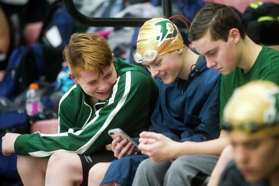 H. H. Dow High School freshmen swimmers Brendan Ladwein, left, Odin Drake, center, and Aaron Brown laugh as they play on their phones before competing in the Pangborn Invitational on Tuesday at Saginaw Valley State University. For more photos from the swim meet, check today's sports section. (Katy Kildee/kkildee@mdn.net)