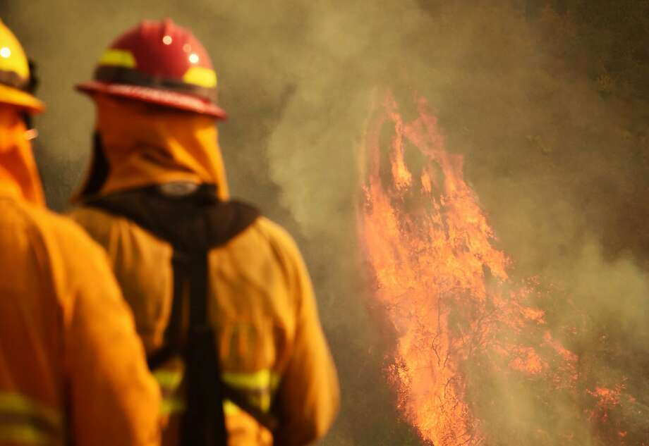 Firefighters keep an eye on burning vegetation Wednesday in Montecito, near Santa Barbara, as the Thomas Fire spreads. Photo: Mike Eliason, Associated Press