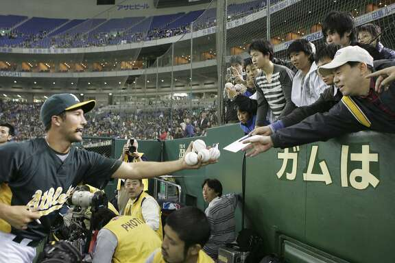 Oakland Athletics pitcher Huston Street reaches out to give fans balls signed with his autographs prior to their exhibition baseball game against Japan's Yomiuri Giants at Tokyo Dome in Tokyo, Saturday, March 22, 2008.  (AP Photo/Koji Sasahara)