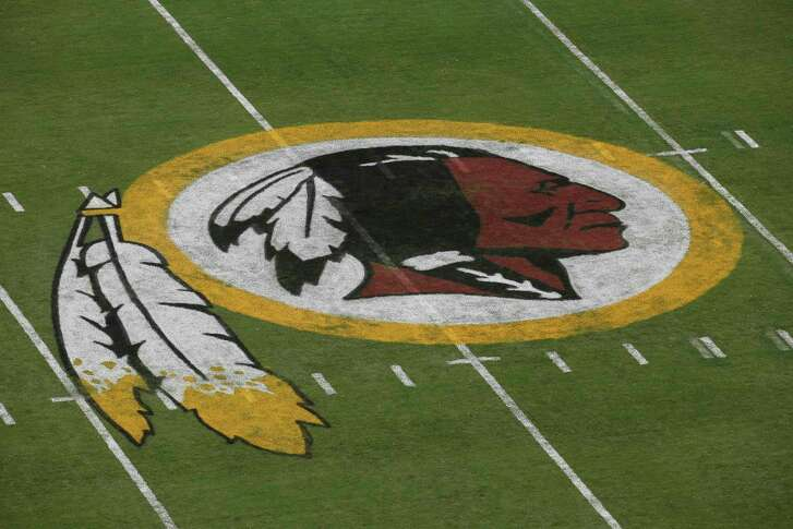 FILE - In this Aug. 7, 2014 file photo, the Washington Redskins logo is seen on the field before an NFL football preseason game against the New England Patriots in Landover, Md.  A federal judge has ordered the Patent and Trademark Office to cancel registration of the Washington Redskins' trademark, ruling that the team name may be disparaging to Native Americans. The ruling Wednesday by Judge Gerald Bruce Lee affirms an earlier finding by an administrative appeal board.