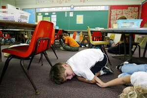 OAHU, HI - FEBRUARY 18: Kindergarten students lie on the floor during a classroom lockdown drill February 18, 2003 in Oahu, Hawaii. Lockdown procedure is used to protect school children from possible threats on campus such as intruders, terrorism or military attack. (Photo by Phil Mislinski/Getty Images)