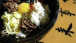 Dolsot bibimbap is a Korean classic rice bowl with bulgogi, greens, daikon radish, mushrooms, carrots, bean sprouts and an egg served in a superheated stone bowl at Seoul Asian Market & Cafe.