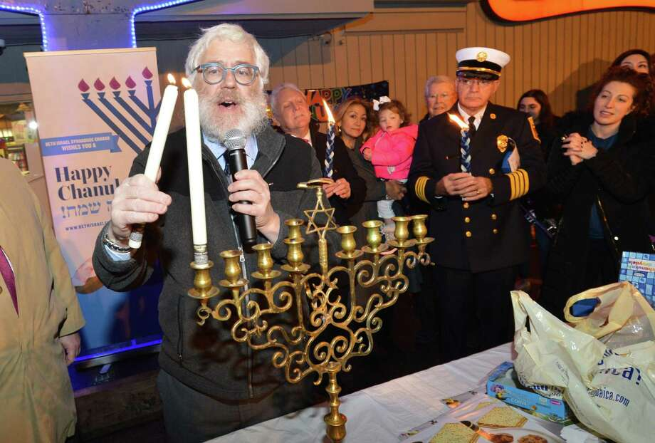 Rabbi Yehoshua S. Hecht, of Beth Israel Synagogue Chabad of Westport/Norwalk, lights the menorah celebrating Hanukkah during a ceremony at Stew Leonard's in Norwalk on Tuesday. The 26th annual menorah lighting celebration included live music, holiday song and dance and complimentary Kosher refreshments and juice. Traditional dreidels and chocolate gelt were passed out for all. Photo: Alex Von Kleydorff / Hearst Connecticut Media / Norwalk Hour
