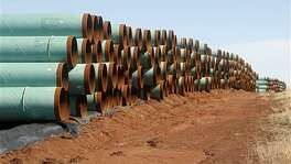 In this Feb. 1, 2012 photo, miles of pipe for the Canada-to-Texas Keystone XL pipeline are stacked in a field near Ripley, Okla. Pipeline companies are fighting to maintain tax breaks that allow them to deduct the borrowing costs on construction projects that take years to permit and build.