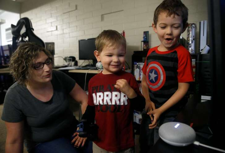 Nina Martin and her two boys, Bradley, 2, and Colin, 5, interact with their Google Home Mini smart speaker in Concord, Calif. on Friday, Dec. 8, 2017.