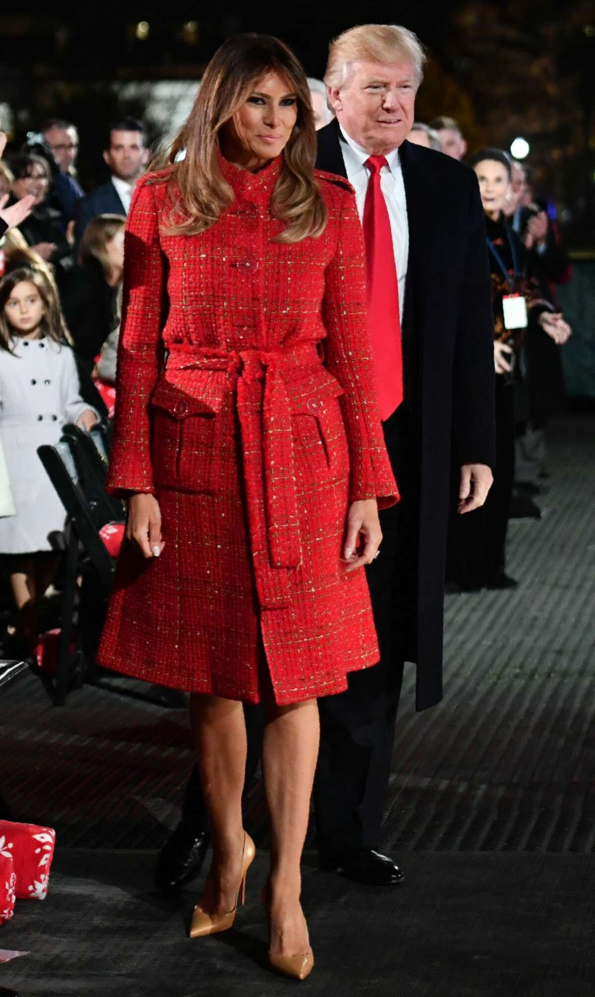 US President Donald Trump and First Lady Melania Trump walk to the stage during the 95th annual National Christmas Tree Lighting ceremony at the Ellipse in President's Park near the White House in Washington, D.C on November 30, 2017.