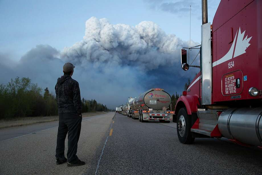 Drivers of a resupply convoy stand outside their vehicles south of Fort McMurray, Canada, as a wildfire blocked the only highway to the city in northern Alberta in May 5, 2016. Photo: TYLER HICKS, NYT