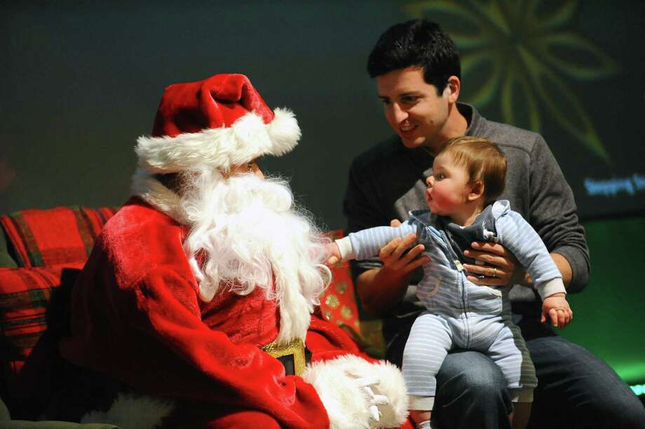 Eight-month-old Ryan Herman, of Westport, reaches to touch Santa Claus while being held by his dad Greg Herman during a meet and greet with Santa inside Stepping Stones Museum in Norwalk Dec. 10. Photo: Michael Cummo / Hearst Connecticut Media / Stamford Advocate