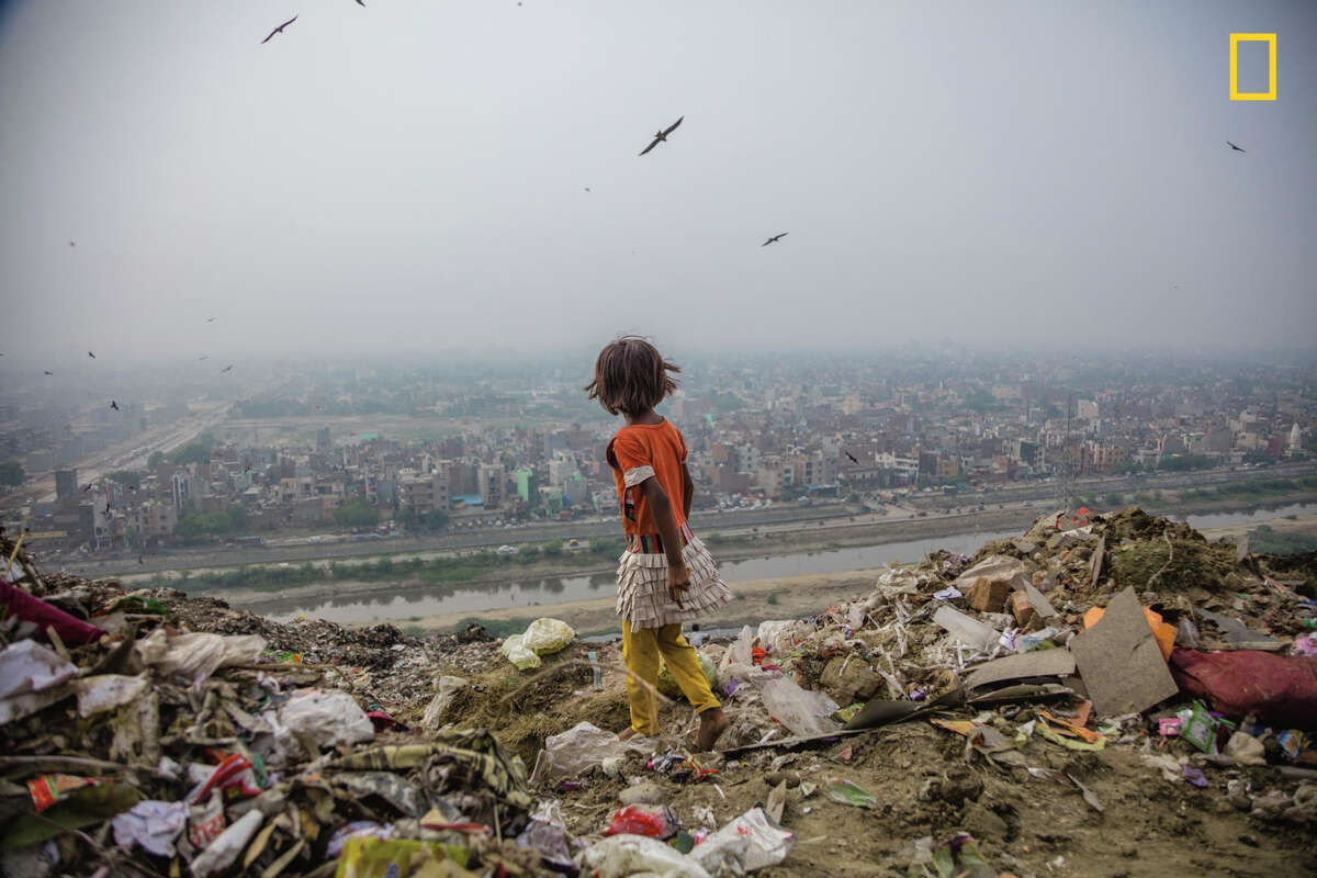 Ghazipur landfill, 70 acres of trash in Delhi, India, provides a hunting ground for seven-year-old Zarina, who salvages items to sell. Like girls in many parts of the world, she lives in poverty with little access to education.This photo was originally published in