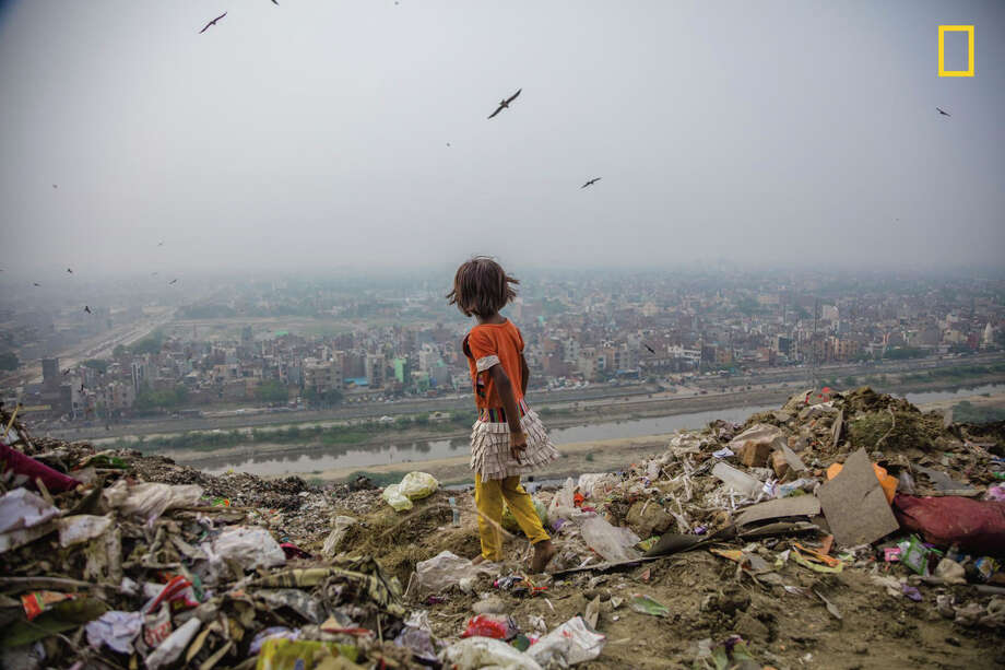 "Ghazipur landfill, 70 acres of trash in Delhi, India, provides a hunting ground for seven-year-old Zarina, who salvages items to sell. Like girls in many parts of the world, she lives in poverty with little access to education.This photo was originally published in ""For These Girls, Danger Is a Way of Life,"" in January 2017. Photo: STEPHANIE SINCLAIR, NATIONAL GEOGRAPHIC"
