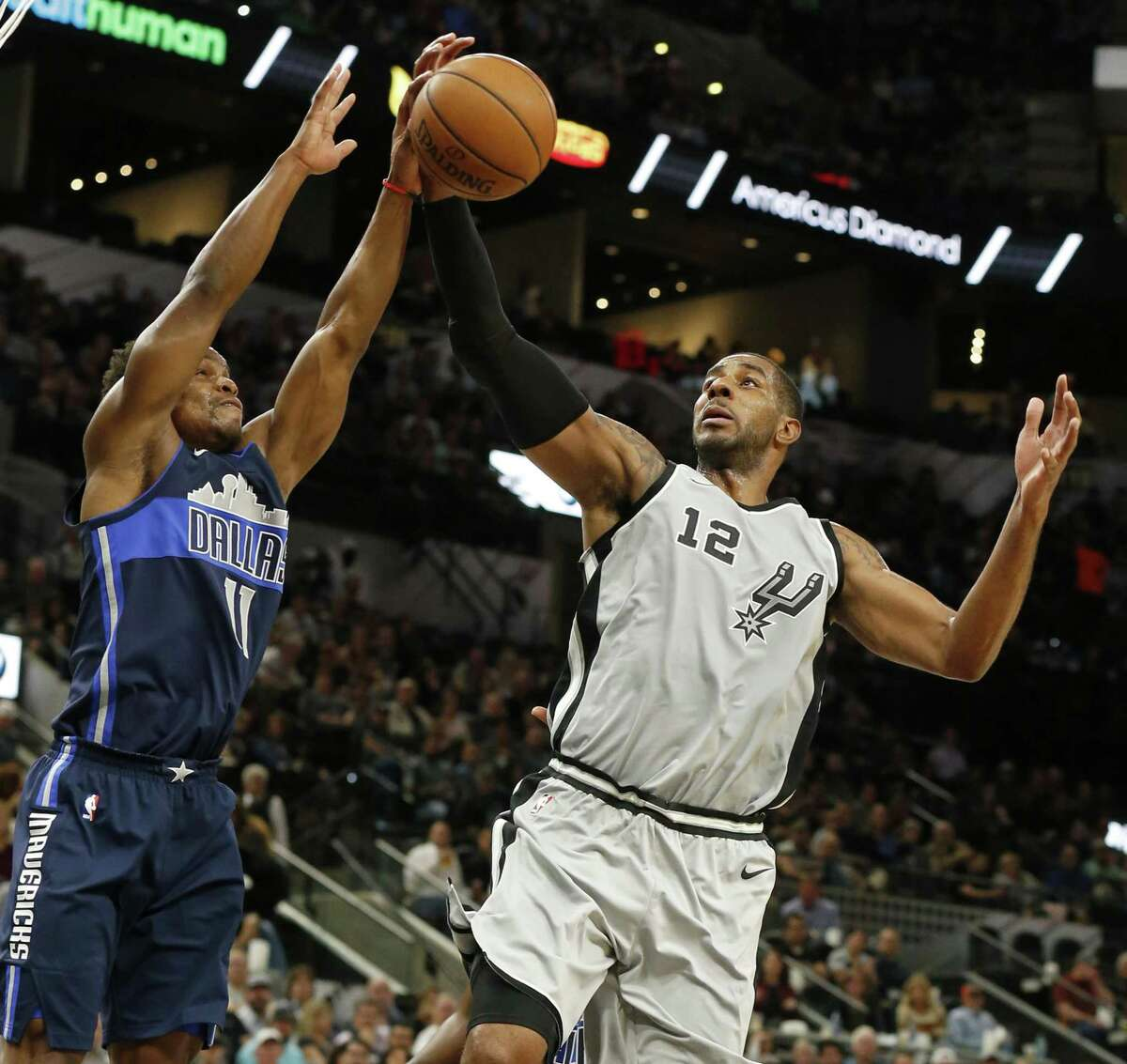 Dallas Mavericks Yogi Ferrell and San Antonio Spurs' LaMarcus Aldridge grab for a rebound during first half action Monday Nov. 27, 2017 at the AT&T Center.