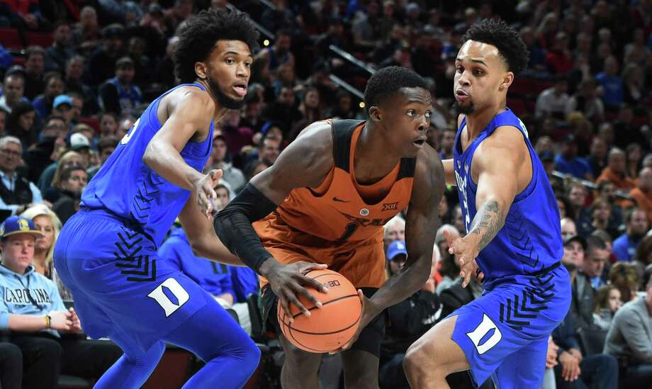 Texas' Andrew Jones (center), shown against Duke's Marvin Bagley III (left) and Gary Trent Jr., fractured his wrist Dec. 5. Coach Shaka Smart believes he'll be out at least through Christmas. Photo: Steve Dykes / Getty Images / 2017 Getty Images