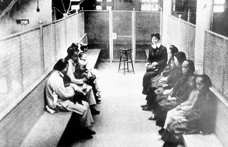 ADVANCE FOR MONDAY, APRIL 8--FILE--A group of Chinese and Japanese women wait in a wire mesh enclosure for processing at the Angel Island barracks in this file photo from the late 1920s. The Island was the site of the Angel Island Immigration Station, California's version of Ellis Island, which processed one million immigrants from 1910 to 1040, mostly from China and Japan. (AP Photo/Files)