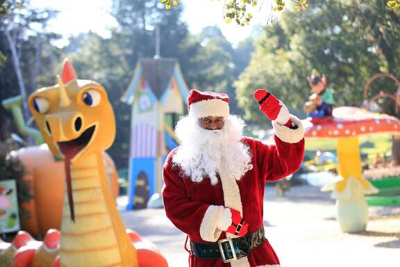 Eric Martin, Fairyland's Santa Claus, poses for a portrait next to Happy Dragon at Fairyland  on Thursday, December 14, 2017 in Oakland, Calif.