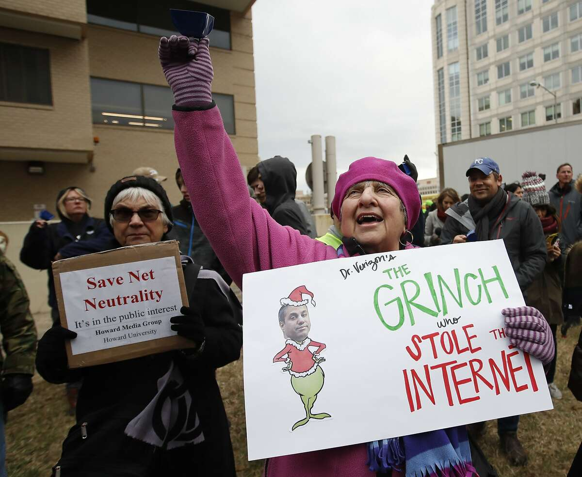 """Diane Tepfer holds a sign with an image of Federal Communications Commission (FCC) Chairman Ajit Pai as the """"Grinch who Stole the Internet"""" as she protests near the FCC, in Washington, Thursday, Dec. 14, 2017. The FCC voted to eliminate net-neutrality protections for the internet. (AP Photo/Carolyn Kaster)"""