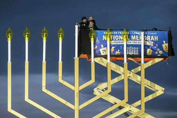 Left to right, Rabbi Levi Shemtov, National Economic Director Gary Cohn, and Rabbi Abraham Shemtov light the Menorah during the annual National Menorah Lighting, in celebration of Hanukkah, on the Ellipse near the White House on Tuesday.