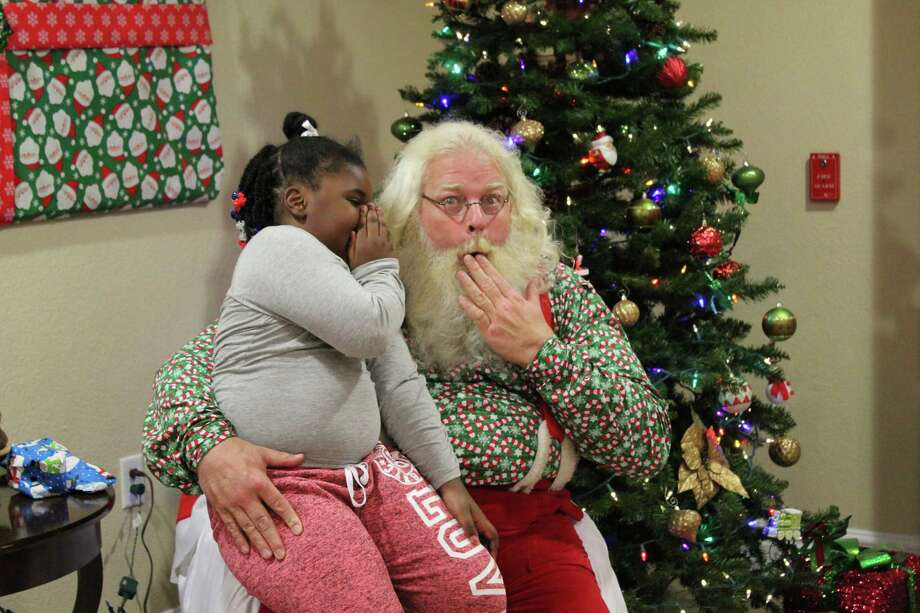 A girl whispers a secret to Santa Phil during his visit to Candlewood Suites in Kingwood on Tuesday, Dec. 12. Photo: Melanie Feuk