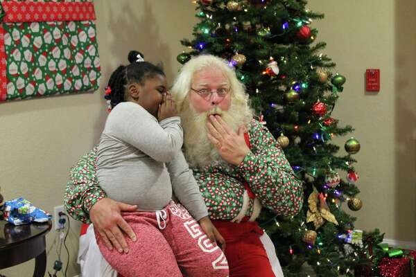 A girl whispers a secret to Santa Phil during his visit to Candlewood Suites in Kingwood on Tuesday, Dec. 12.