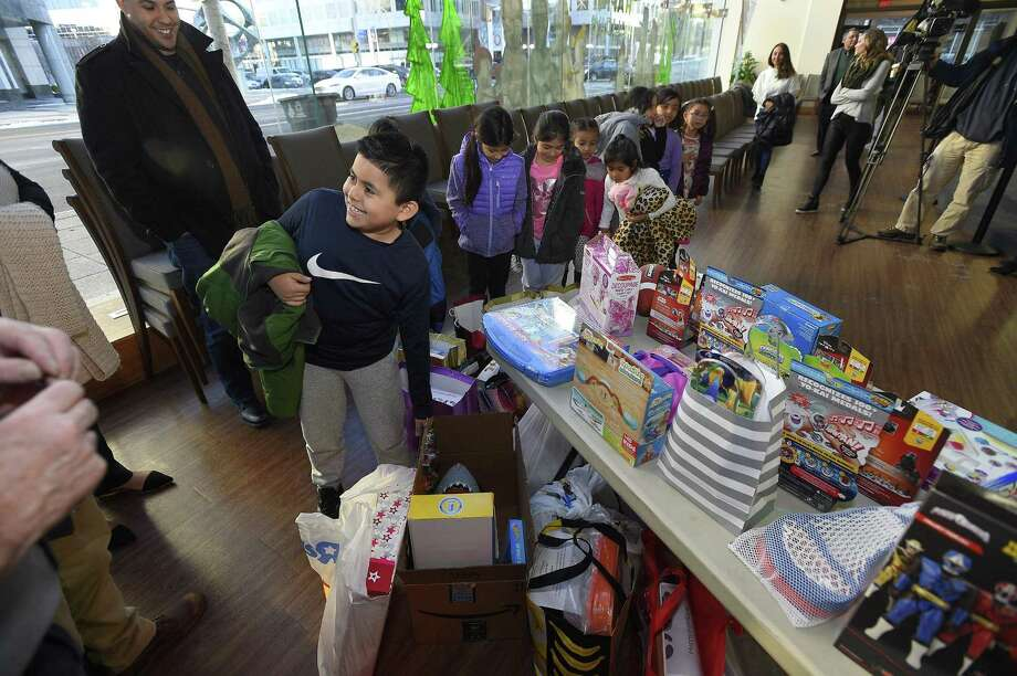 "Randy Lopez Monterrozo, 8, one of nine children from the Boys and Girls Club of Stamford checks out some of the 150 toys collected by NBCUniversal employees, as part of the company's annual Holiday Toy Drive, at the Stamford Media Studio in Stamford, Conn. on Dec. 14, 2017. Employees participating in the toy drive received a personalized ""wish card"" from a child who participates in the clubs after school program that specified which toy he or she would like to receive. in addition to the wish card program, NBCUniversal purchased extra toys to be donated to other children at the club. Photo: Matthew Brown / Hearst Connecticut Media / Stamford Advocate"