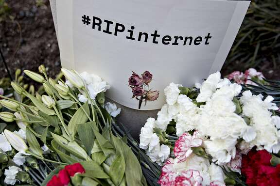 "A ""#RIPinternet"" sign stands outside the Federal Communications Commission (FCC) headquarters ahead of a open commission meeting in Washington, D.C., U.S., on Thursday, Dec. 14, 2017. The FCC is slated to vote to roll back a 2015 utility-style classification of broadband and a raft of related net neutrality rules, including bans on broadband providers blocking and slowing lawful internet traffic on its way to consumers. Photographer: Andrew Harrer/Bloomberg"