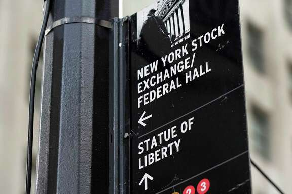 A street sign directs people to the New York Stock Exchange.