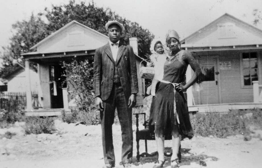 Loil Ellison and wife, Estella Ellison, and daughter Estella Mae Ellison stand in front of their house at 520 Callaghan Ave., in early the 1930s. In the background are shotgun-style houses, across the street at 519 (left) and 521 Callaghan Ave., in a neighborhood demolished to make way for the Victoria Courts public housing project. Photo: Courtesy UTSA Special Collections