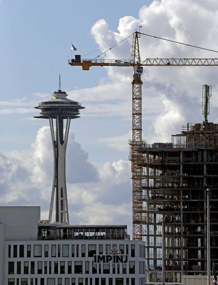 A construction crane in view of the Space Needle symbolizes the booming economy in the high-tech hub of Seattle. Photo: Elaine Thompson, Associated Press