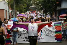 "In this Sept. 30, 2017 photo, members of a gay organization ""Panambi,"" meaning butterfly in Guarani, protest the killing of transvestite prostitutes and demand equal rights for gays during the annual LGBQT parade in Asuncion, Paraguay. Discrimination against gay and transgender people has traditionally been the norm in Paraguay, and activists say it's becoming more evident since the conservative government recently banned the teaching of sexual diversity in schools. (AP Photo/Jorge Saenz)"
