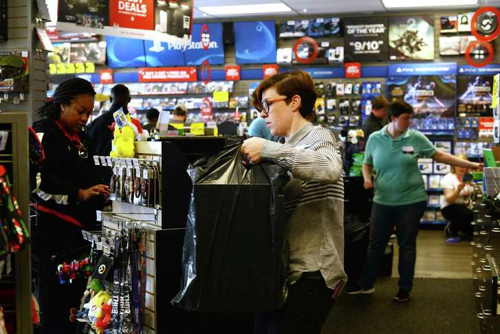 Store leader Shelley Merritt, center, takes a bag to Jessica Jones last month at a Game Stop in Kinston, N.C.