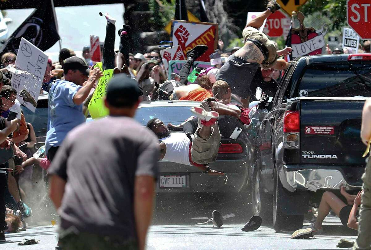 FILE - In this Aug. 12, 2017 file photo, people fly into the air as a vehicle is driven into a group of protesters demonstrating against a white nationalist rally in Charlottesville, Va. James Alex Fields Jr., the man accused of driving into the crowd demonstrating against a white nationalist protest, killing one person and injuring many more, has a preliminary court hearing Thursday, Dec. 14, 2017. (Ryan M. Kelly/The Daily Progress via AP, File)