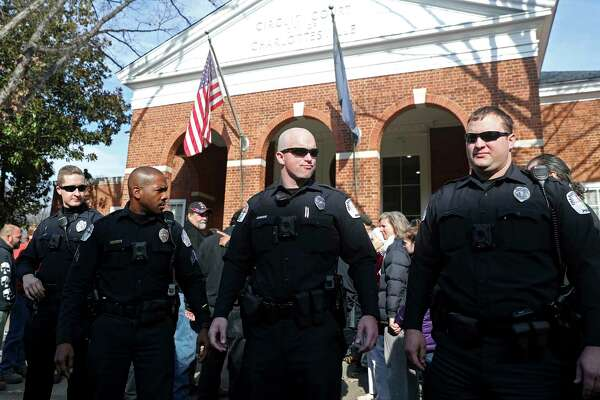 Police officers block the front of the Charlottesville Circuit Court building ahead of the preliminary hearing for James Fields on Thursday on Thursday, Dec. 14, 2017 in Charlottesville, Va. Fields is accused of driving into a crowd of counterprotesters at a white nationalist rally in August. (Zack Wajsgras/The Daily Progress via AP)