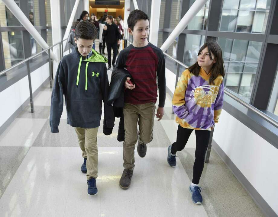 Luke McQuillan, center, 12, of Riverside, walks the halls with his friends Miles Trager, 12, of Riverside, and Caroline Frankel, 12, of Riverside, during a tour of Yale New Haven Children's Hospital in New Haven on Thursday. McQuillan, a seventh-grader at Eastern Middle School, battled brain cancer and finished his radiation and chemotherapy treatments three and a half years ago. He collected more than $12,000 worth of toys and items for kids at the Yale New Haven Children's Hospital and presented them on Thursday while giving his friends and family a tour of the facility. Photo: Tyler Sizemore / Hearst Connecticut Media / Greenwich Time