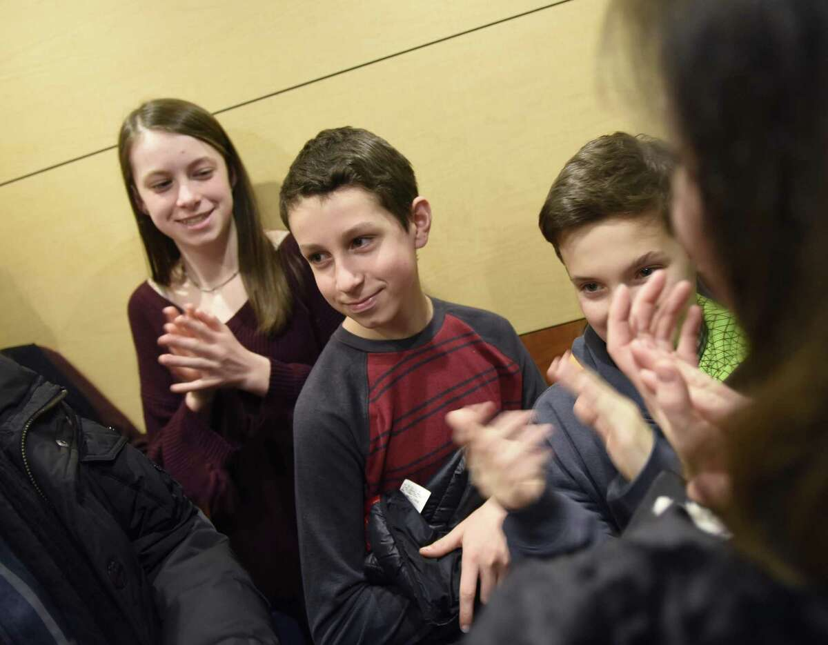 Luke McQuillan, center, 12, of Riverside, gets a round of applause from his sister, Genna, 15, friend Nicholas O'Brien, 12, of Riverside, and others during a tour of Yale New Haven Children's Hospital in New Haven, Conn. Thursday, Dec. 14, 2017. McQuillan, a seventh-grader at Eastern Middle School, battled brain cancer and finished his radiation and chemotherapy treatments three and a half years ago. He collected more than $12,000 worth of toys and items for kids at the Yale New Haven Children's Hospital and presented them on Thursday while giving his friends and family a tour of the facility.