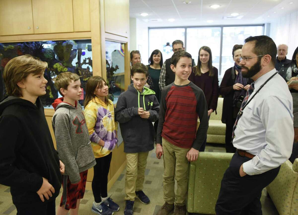 From left, Gaston Gomez, 13, of Old Greenwich, Nicholas O'Brien, 12, of Riverside, Caroline Frankel, 12, of Riverside, Miles Trager, 12, of Riverside, and Luke McQuillan, 12, of Riverside, chat with Dr. Asher Marks, who used to help McQuillan when he had cancer, during a tour of Yale New Haven Children's Hospital in New Haven, Conn. Thursday, Dec. 14, 2017. McQuillan, a seventh-grader at Eastern Middle School, battled brain cancer and finished his radiation and chemotherapy treatments three and a half years ago. He collected more than $12,000 worth of toys and items for kids at the Yale New Haven Children's Hospital and presented them on Thursday while giving his friends and family a tour of the facility.