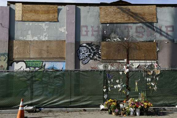 Flowers are left at a makeshift memorial outside  the Ghost Ship warehouse in Oakland to 36 partygoers who died there.